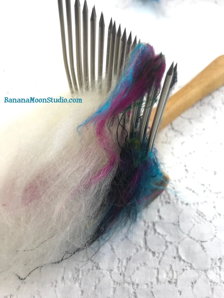 Blending recycled sari silk and blue faced leicester with wool combs. The sari silk gets stuck in the tines. Banana Moon Studio.