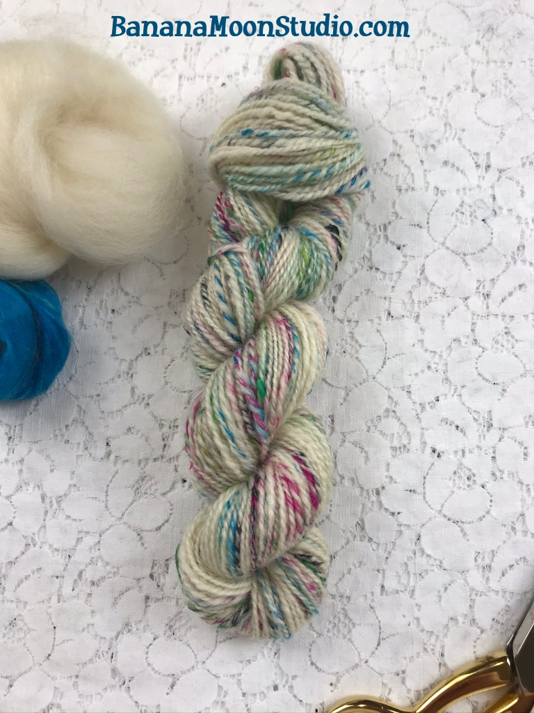 Handspun two ply yarn made with BFL and recycled sari silk. Fibers combined by drafting together. Banana Moon Studio.