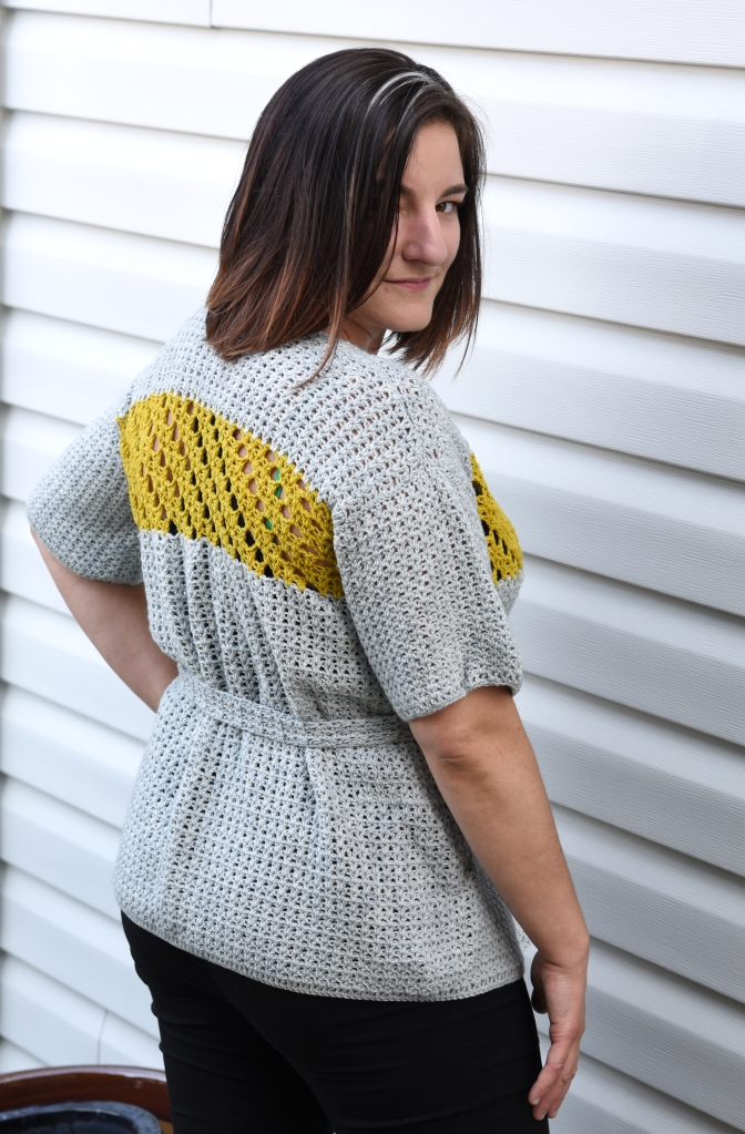 Jessamine Cardigan, a crochet pattern from Banana Moon Studio and Ancient Arts. Back view with belt closure