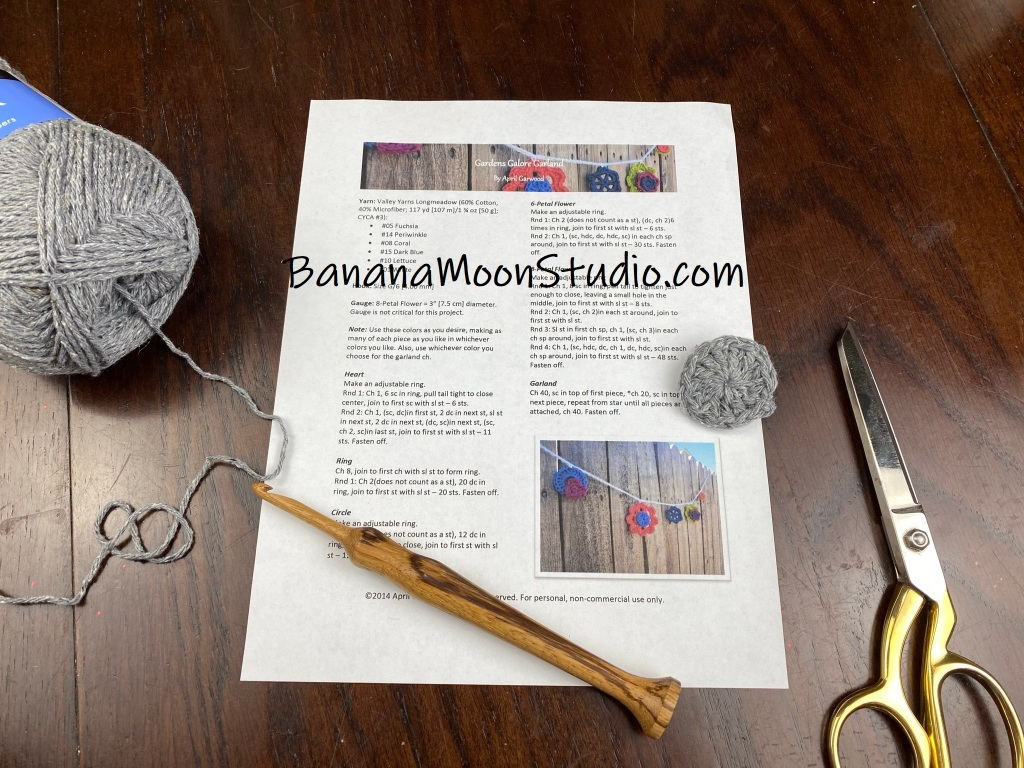 Learn to read written crochet patterns for beginners with this video from Banana Moon Studio! Written crochet pattern on a table, skein of grey yarn, small crochet circle, wooden crochet hook, large metal sewing scissors.