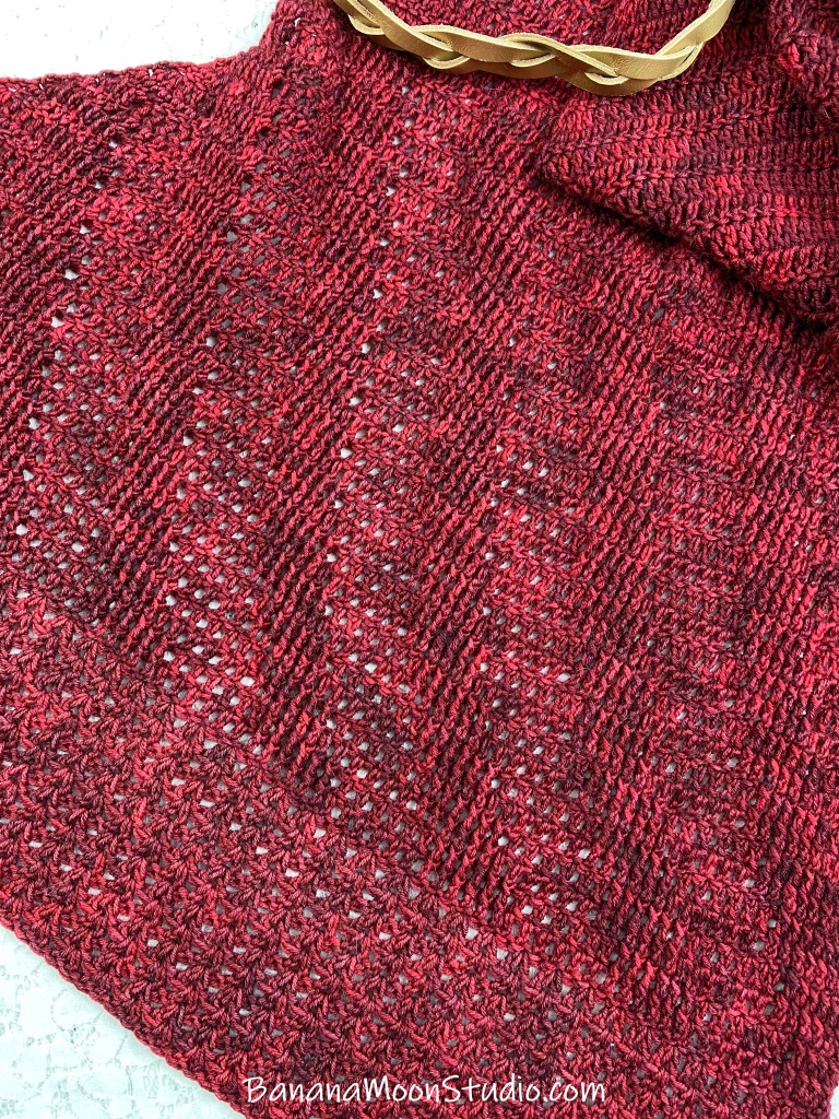 Close up of red crochet shawl with gold leather braid shawl cuff. Codex Alera CAL with Banana Moon Studio and Ancient Arts Yarn.