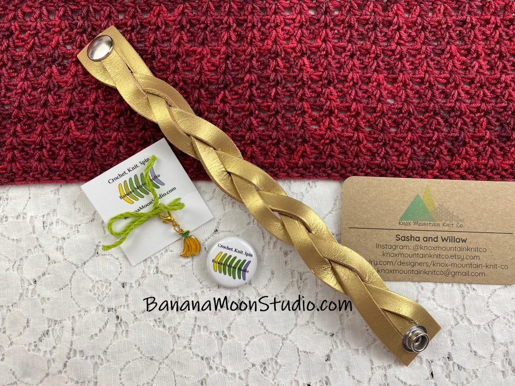 Gold braided leather shawl cuff with snaps on a red shawl and white lace background. Banana Moon Studio stitch marker and button. Knox Mountain Knit Co. business card.