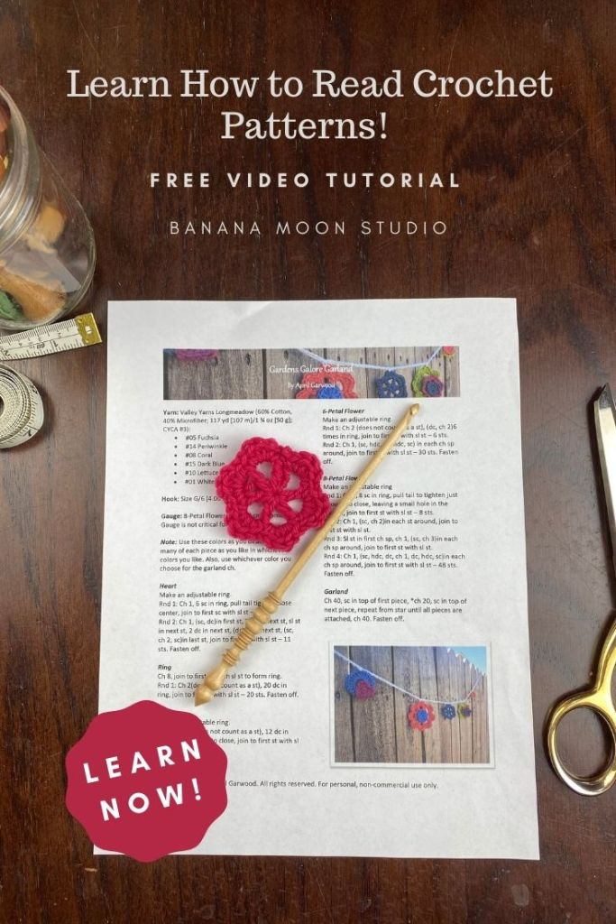 Learn how to read crochet patterns with this free video tutorial from Banana Moon Studio. Written crochet pattern on a table. Wooden crochet hook. Small pink crochet flower. Learn now!