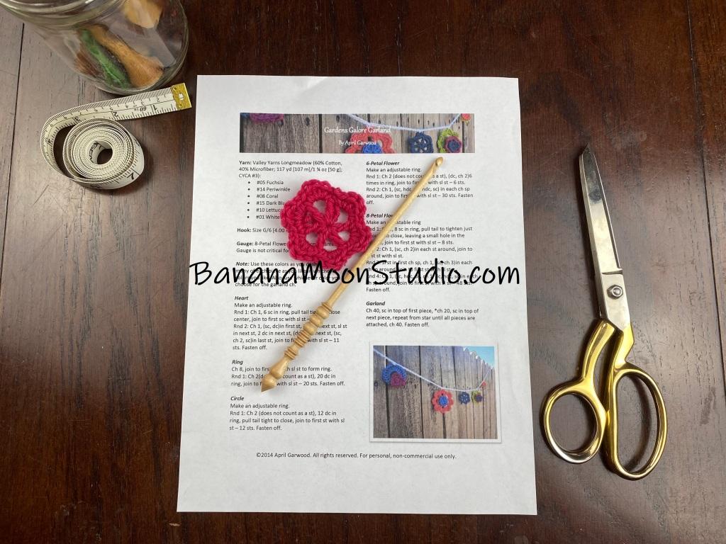 Written crochet pattern on a table with a wooden crochet hook and small pink crochet flower. scissors. measuring tape. Learn to read a crochet pattern with Banana Moon Studio!