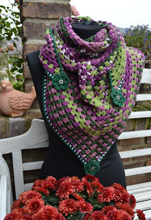 Granny stitch crochet shawl in purple and green on a black mannequin. The shawl has green flowers on each point.
