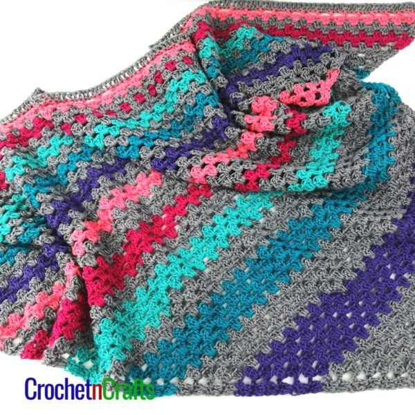 crochet granny stitch shawl with stripes of gray, purple, teal, fuchsia, and pink.